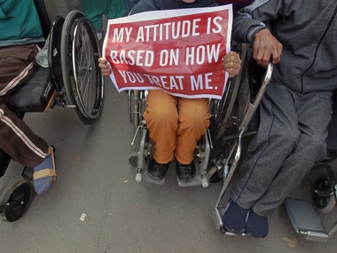 A disabled child holds a placard during a demonstration to mark the World Disability Day in Srinagar
